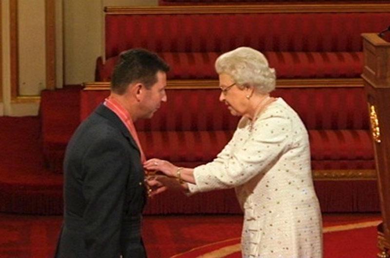 Warren James receiving his CBE from The Queen
